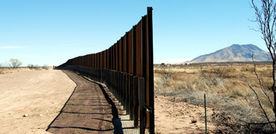 U.S. mexico border fence brown with scenery in background