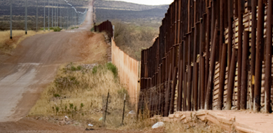 Brown border fence with landscape and road