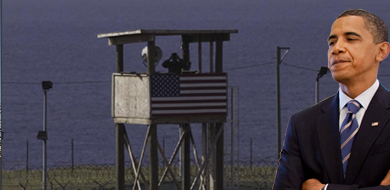 President Obama looking down and background of image has tower at Guantanamo