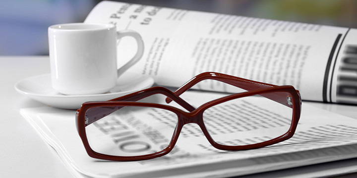 Eyeglasses with newspaper and coffee cup